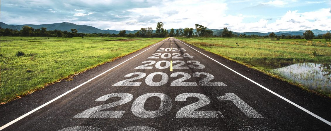 2020-2025 written on highway road in the middle of empty asphalt road at golden sunset and beautiful blue sky. Concept for vision 2020-2025.